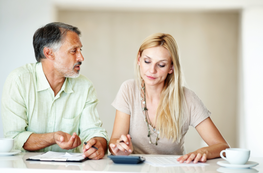 Worried mature man discussing while calculating domestic bills with beautiful woman