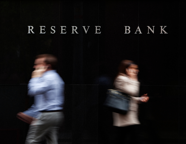 Man and woman walk past each other in front of Reserve Bank