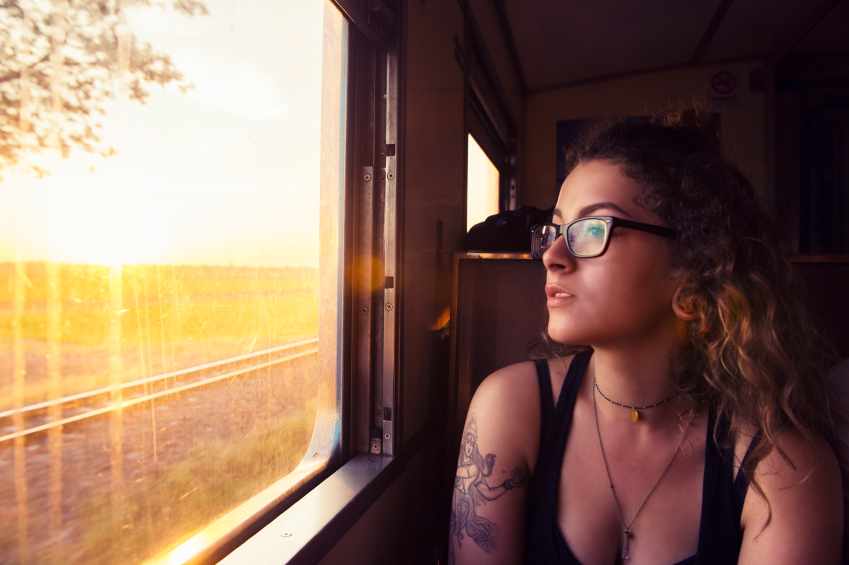 Young woman lady girl with tattoo looking out the window in a train