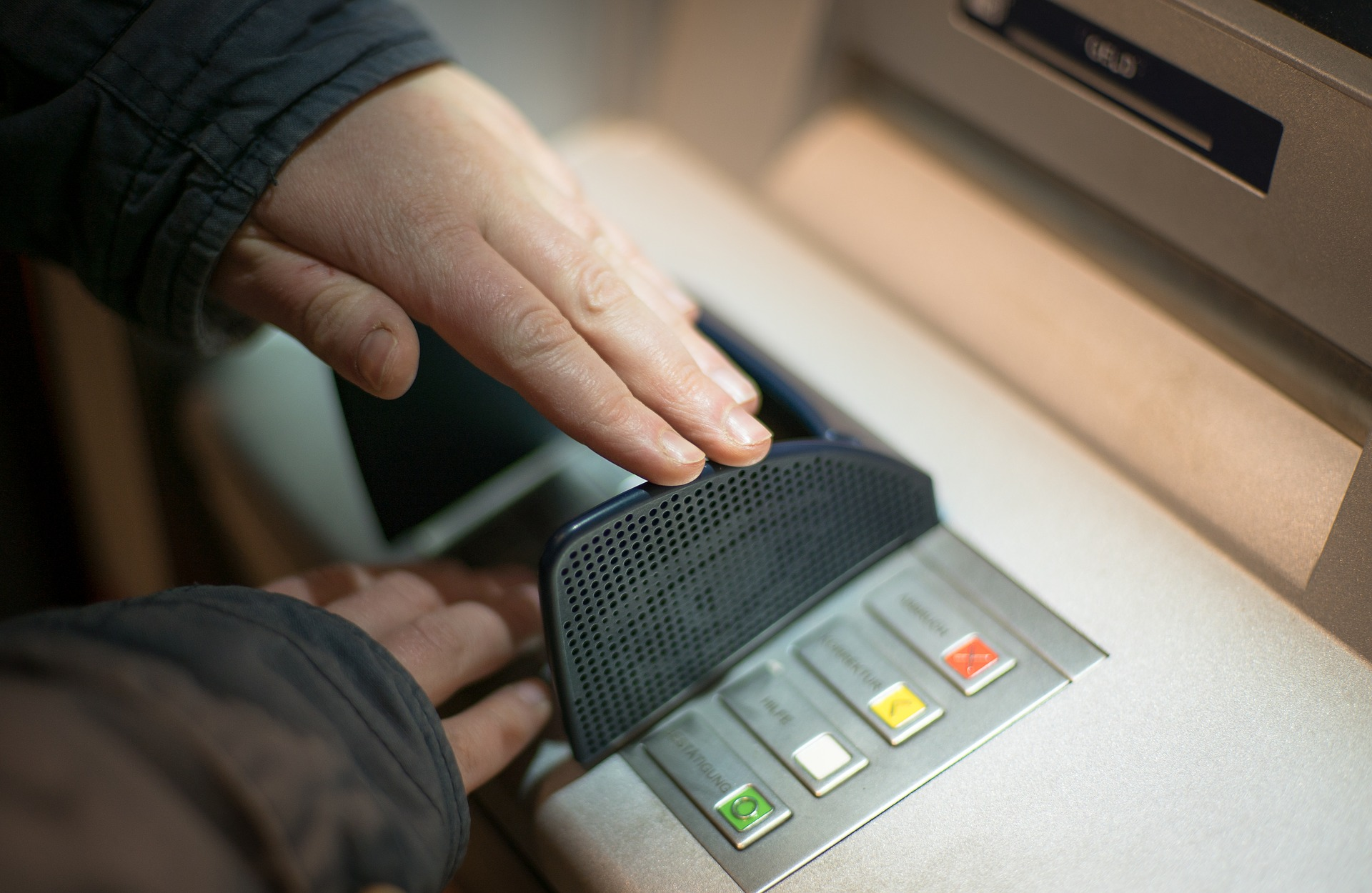 Male hands in black jacket using ATM
